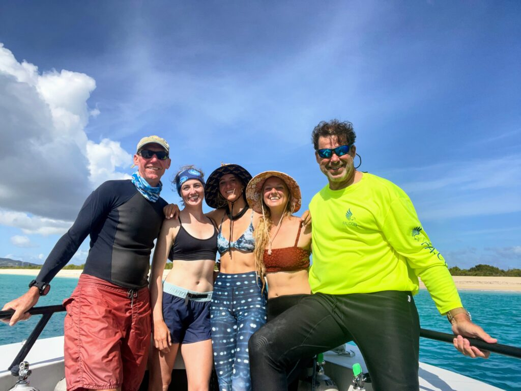 five people on bow of boat in front of sandy beach smiling