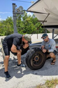 Two men, one bending over and one kneeling, holding and inspecting a damaged car tire on the side of a road